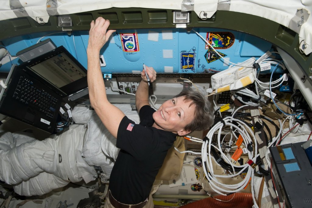 iss050e054558 (03/05/2017) --- NASA astronaut Peggy Whitson signs a bulkhead on the International Space Station next to the Expedition 50 crew patch.